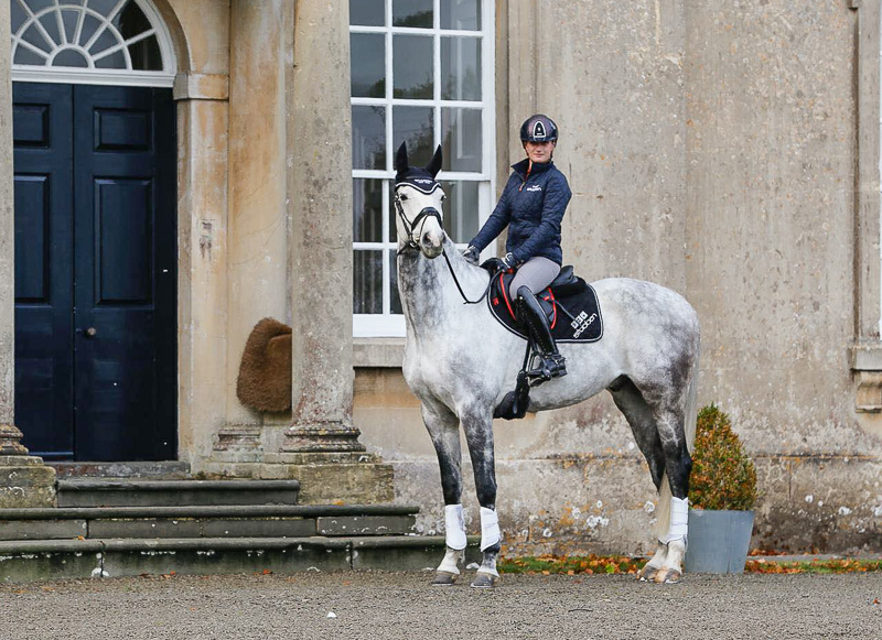 Abi Dean on a grey horse in front of the house